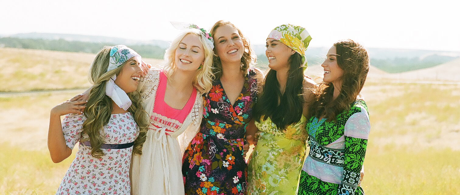 1960s boho floral colorful dresses on models in a field
